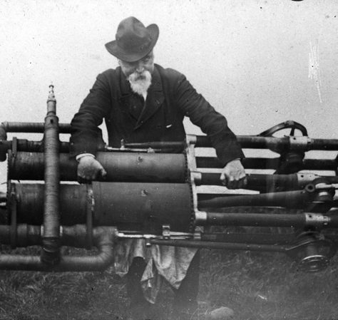 Maxim and his flying machine engine. A grey bearded gentleman in a hat holds a large engine. | Bexley Local Studies & Archive Centre