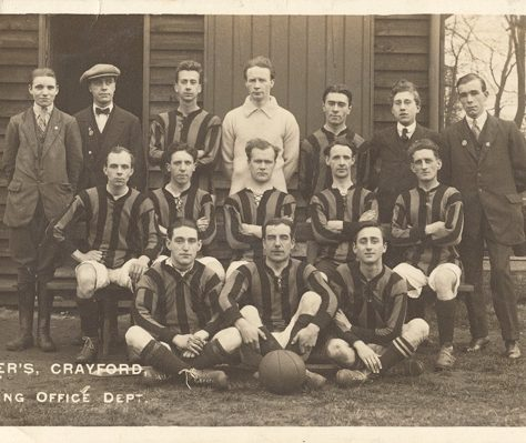 Vickers, Crayford, Drawing Office Dept. Football Team 1917. Three rows of players in striped shirts pose for the photo outside a wooden building, along with training staff. | Bexley Local Studies & Archive Centre