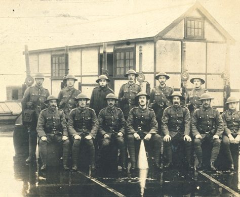 Crayford Volunteer Soldiers, World War I 1914-1918. Two rows of soldiers pose for a photo outside a timber framed building. | Bexley Local Studies & Archive Centre