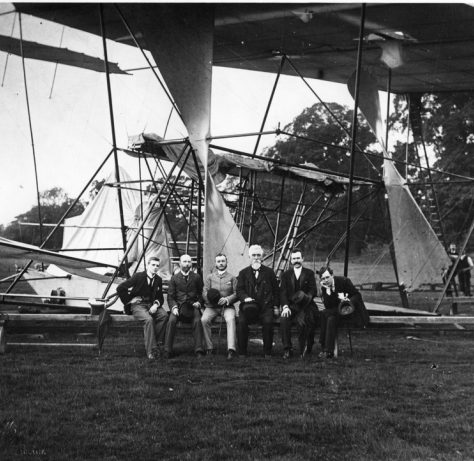Hiram Maxim sitting with dignatories on support rail by his crashed aircraft, Baldwyns Park, 1894 | Bexley Local Studies & Archive Centre