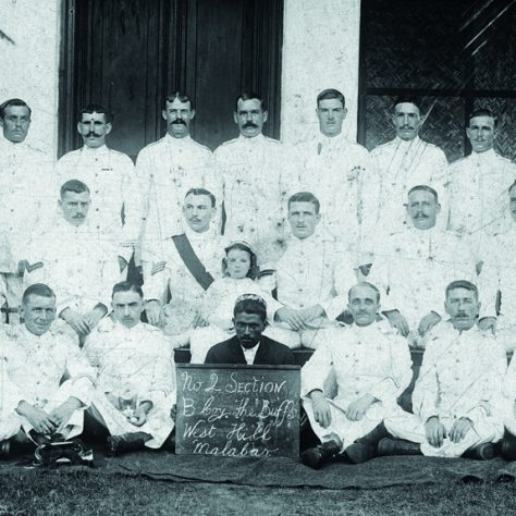 Buffs B Company, Malabar, India. Three rows of men dressed in white. The man centre botton holds a sign, and is dressed in darker colours.