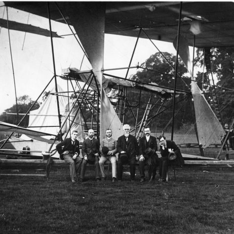 Hiram Maxim sitting with dignatories on support rail by his crashed aircraft, Baldwyns Park, 1894