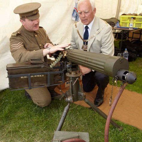 The Mayor looks on. A man in soldier's uniform shows the mayor a replica of a machine gun.