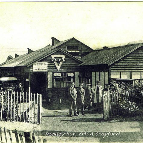 Rodney Hut, YMCA Crayford, c. 1916. Some men stand outside the large wooden structure. A car can be seen to the side of the hut.