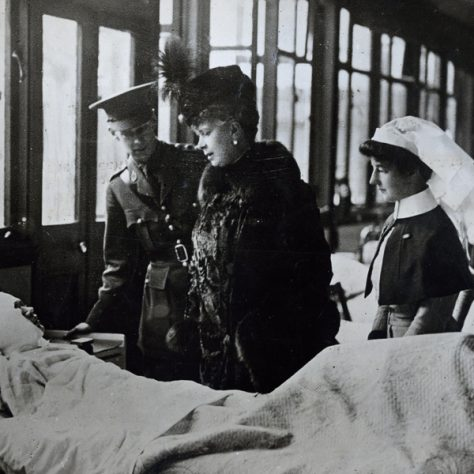 A visit to a wartime hospital. A lady looks on at an injured soldier in bed, surrounded by nurses.