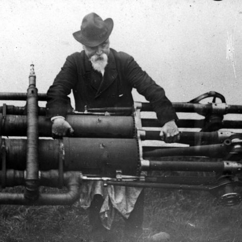 Maxim and his flying machine engine. A grey bearded gentleman in a hat holds a large engine.