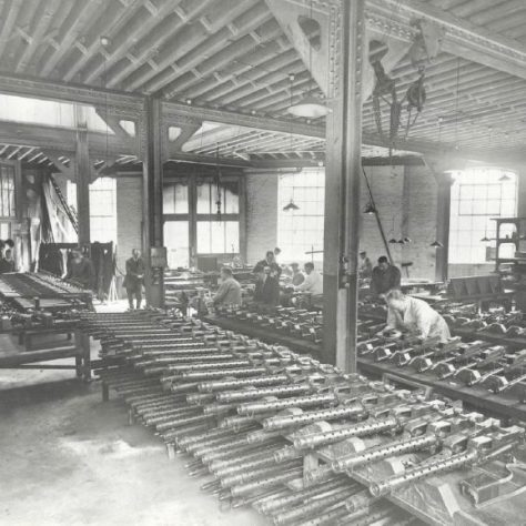 Vickers machine gun factory, Crayford. Workers make the guns, a number of which are laid out.